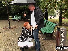 Рыжая шлюха сосет хуй под зонтиком в парке